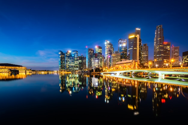 Singapore skyscraper building in downtown district with water reflection at marina bay in night, singapore. Premium Photo