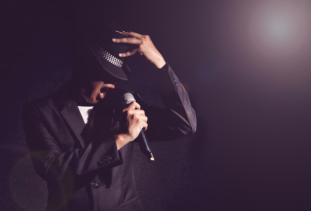 Singer hand holding the microphone and singing on black background Premium Photo
