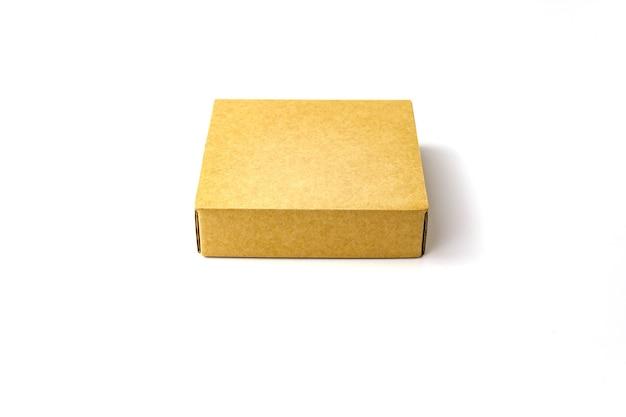 単一の茶色のフラットクラフト紙段ボール箱は白で隔離します。ビューを閉じます。選択的なソフトフォーカス。テキストコピースペース。梱包、輸送、移動の概念 Premium写真