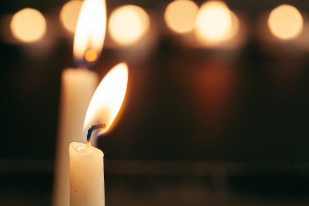A single burning candle isolated with black Premium Photo