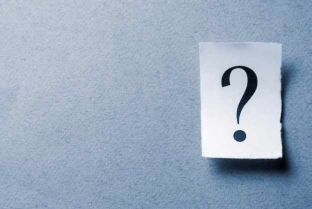 Single curled card with printed question mark Premium Photo