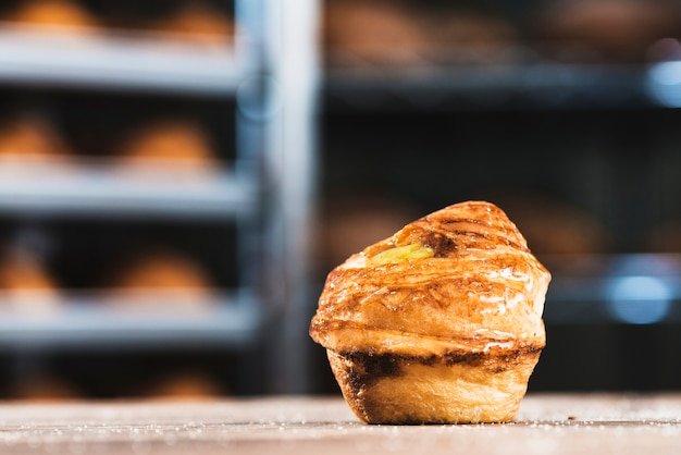 Single fresh baked sweet puff pastry on table Free Photo