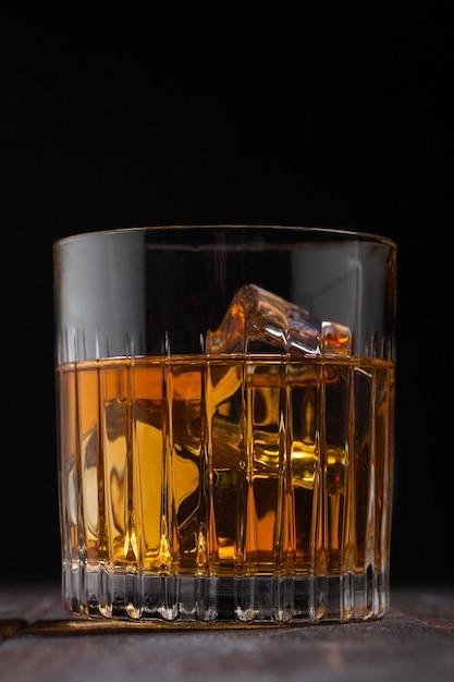 Односолодовый шотландский виски в хрустальном стекле с кубиками льда на поверхности деревянного стола. макрос Premium Фотографии
