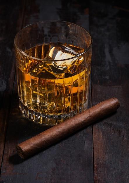 Односолодовый шотландский виски в хрустальных очках с кубиками льда и кубинской сигарой на поверхности деревянного стола. Premium Фотографии