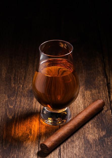 Односолодовый шотландский виски в стекле glencairn с кубинской сигарой на поверхности деревянного стола. вид сверху Premium Фотографии