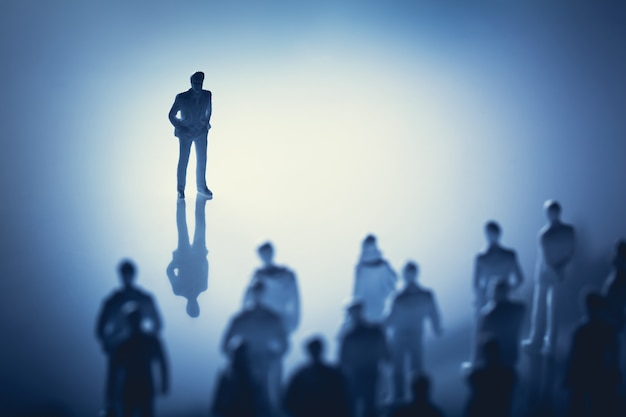 Single man standing in front of group of people. Premium Photo
