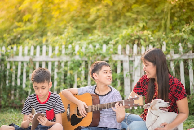 Single mom and sons play guitartogether with fun  in the park Premium Photo