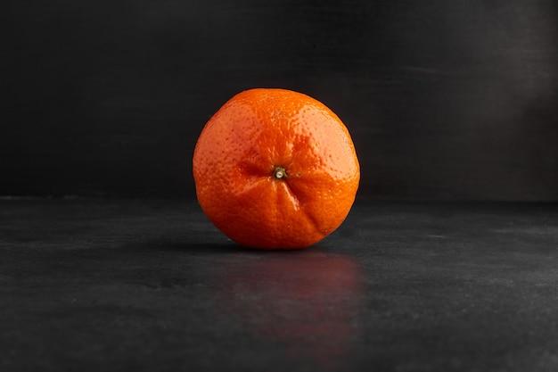 Одиночный апельсин, изолированные на черном фоне. Бесплатные Фотографии