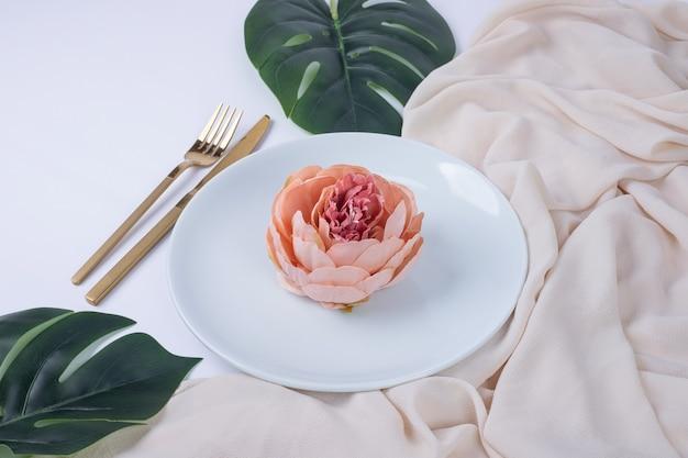 偽の葉とテーブルクロスと白いプレート上のシングルローズ。 無料写真