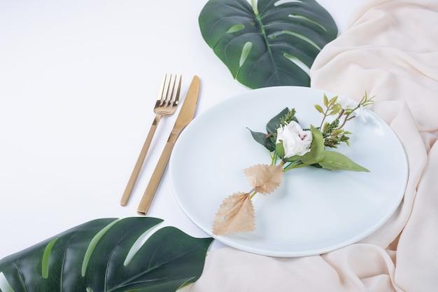 Rosa singola sul piatto bianco con foglie finte e tovaglia. Foto Gratuite