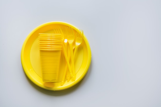 Single use picnic yellow utensils on grey. space for text. Premium Photo