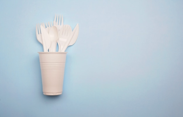 Single-use plastic products: plastic cutlery, cups on bright blue background Premium Photo