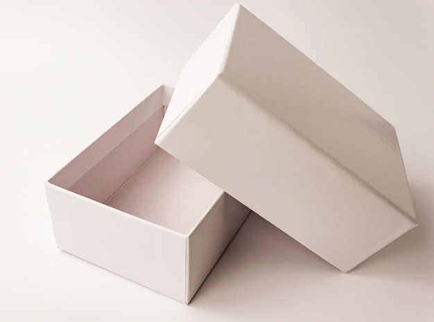 Single white color paper cardboard box on light . close up view. selective soft focus. text copy space. packing, transportation, moving, present concept Premium Photo