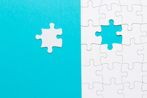 파란색 배경에 단일 흰색 직소 퍼즐 조각 무료 사진
