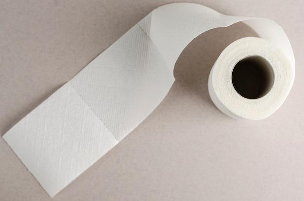 Single white toilet paper roll on grey Premium Photo