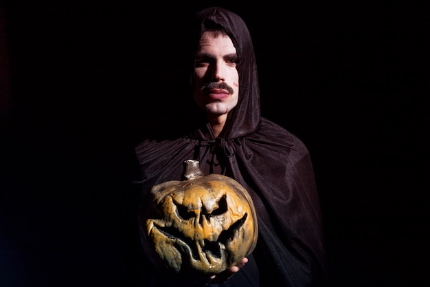 Sinister man with scary pumpkin Free Photo