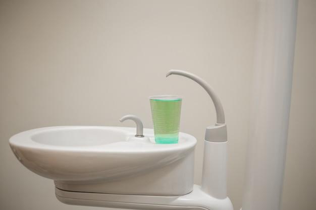 Раковина со стаканом воды в стоматологическом кабинете Premium Фотографии