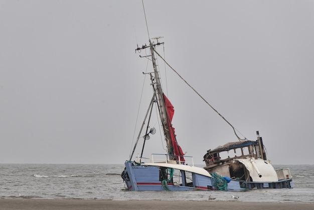 Affondamento nave abbandonata in riva al mare sotto il cielo limpido Foto Gratuite