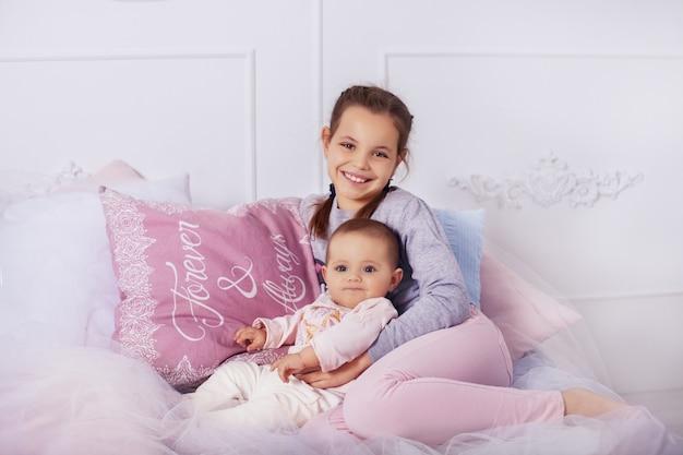 Sister hugs little sister. childhood and education. Premium Photo