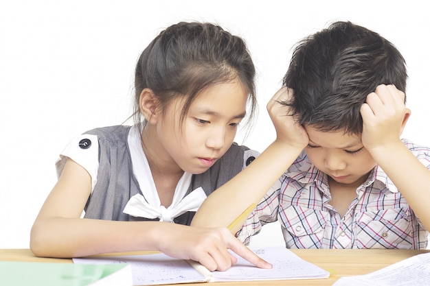 Sister try to teach her naughty younger brother to do homework Free Photo