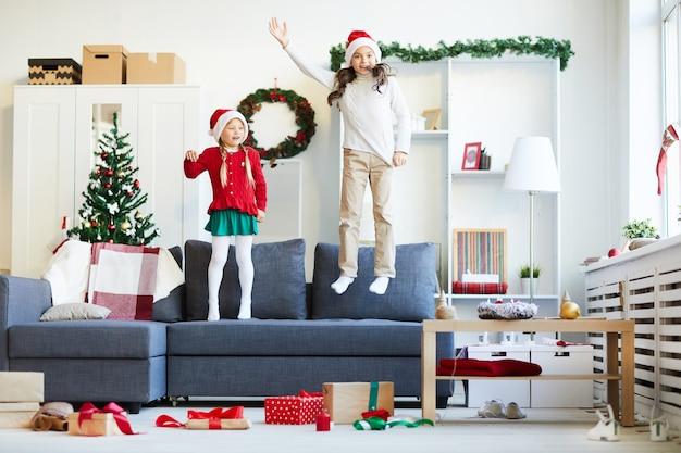 자매 점프와 소파에서 놀고, 산타 모자와 소녀 무료 사진