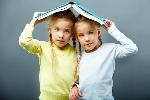Sisters using an open book as an umbrella Free Photo