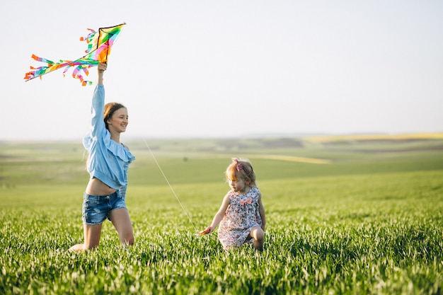 Sisters with kite in field Free Photo