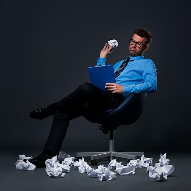 Сидящий бизнесмен бросает на пол мятую бумагу с плохими идеями Бесплатные Фотографии
