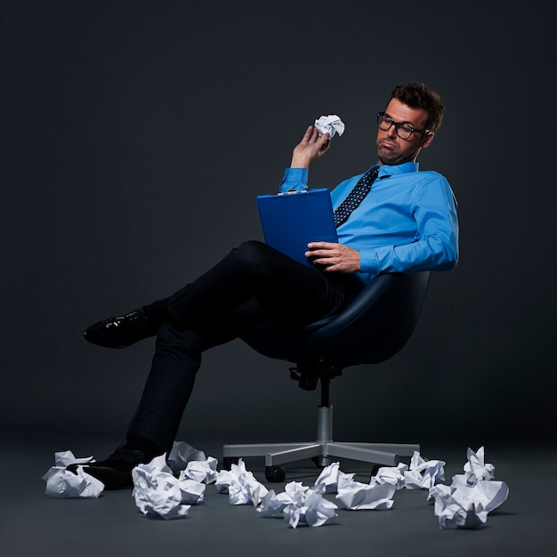 Sitting businessman throwing a crumpled paper with bad ideas on the floor Free Photo