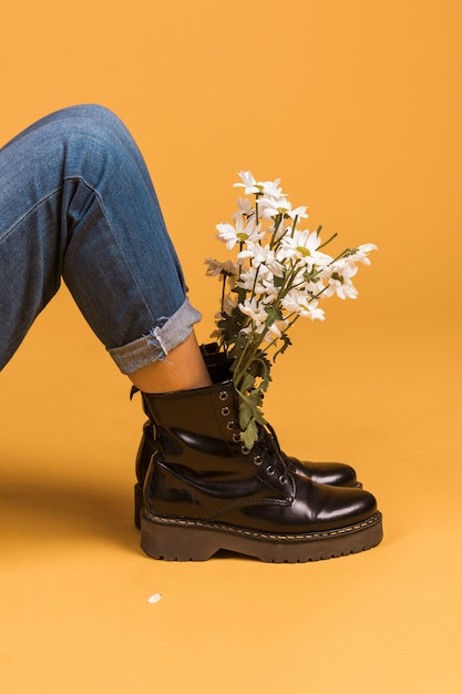 Sitting female legs in boots with flowers inside Free Photo