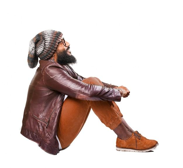 Sitting man clutching his knees Free Photo