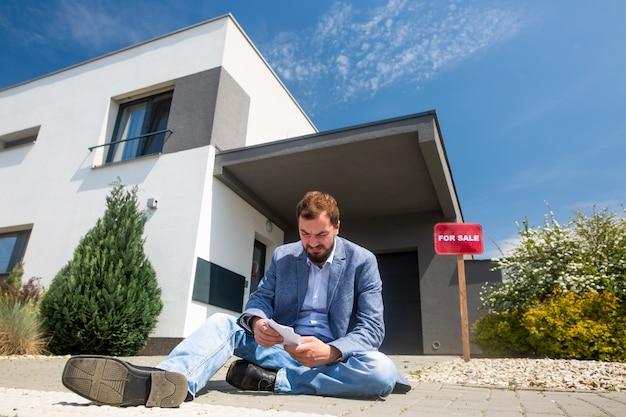 Сидящий мужчина без работы перед домом во время экономического кризиса, продажа недвижимости Premium Фотографии