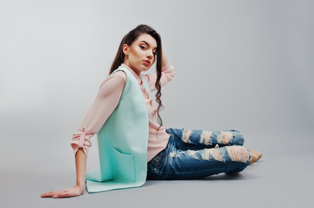 Sitting portrait young brunette girl wearing in pink blouse, turquoise jacket, ripped jeans and cream shoes on gray background Premium Photo