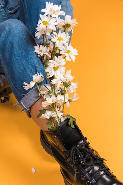 Sitting womans legs in boots with flowers bouquet inside Free Photo
