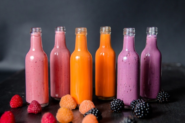 Six bottles with berry smoothies with fresh berries Premium Photo