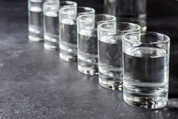 Six shots of vodka in a row. copy space Premium Photo