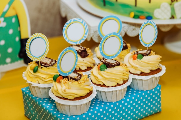 Six yellow cupcakes with pieces of paper for text Premium Photo