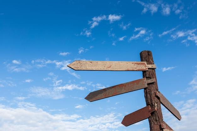 空の木の矢印の形のサイン、青い空、古い木製の方向のサイン、青のsk Premium写真