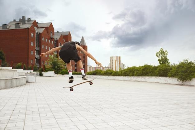 曇りの日に街の通りでトリックをしているスケートボーダー 無料写真