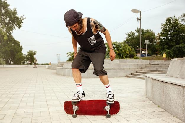 Скейтбордист делает трюк на улице города в пасмурный день Бесплатные Фотографии