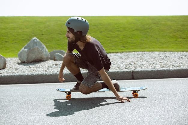 Скейтбордист делает трюк на улице города в солнечный день. молодой человек в снаряжении верховой езды и лонгбординга на асфальте в действии. концепция досуга, спорта, экстрима, хобби и движения. Бесплатные Фотографии