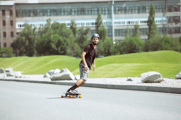화창한 날에 도시의 거리에서 트릭을하는 스케이트 보더 무료 사진