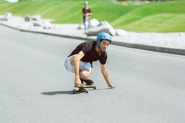 화창한 날에 도시의 거리에서 트릭을하고있는 스케이트 보더. 무료 사진