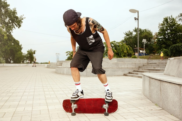 Skateboarder doing a trick at the city's street in cloudly day Free Photo