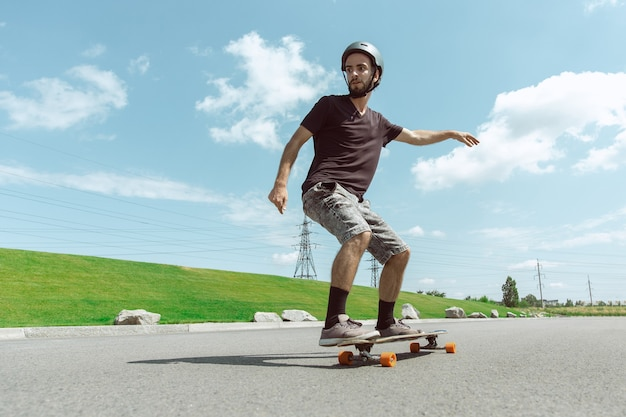 Skateboarder doing a trick at the city's street in sunny day. young man in equipment riding and longboarding near by meadow in action. concept of leisure activity, sport, extreme, hobby and motion. Free Photo