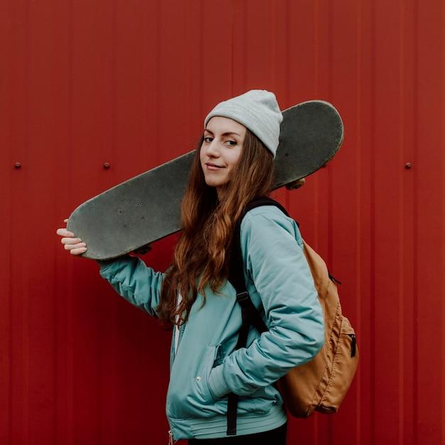 Ragazza di skateboarder e il suo skate in città Foto Gratuite