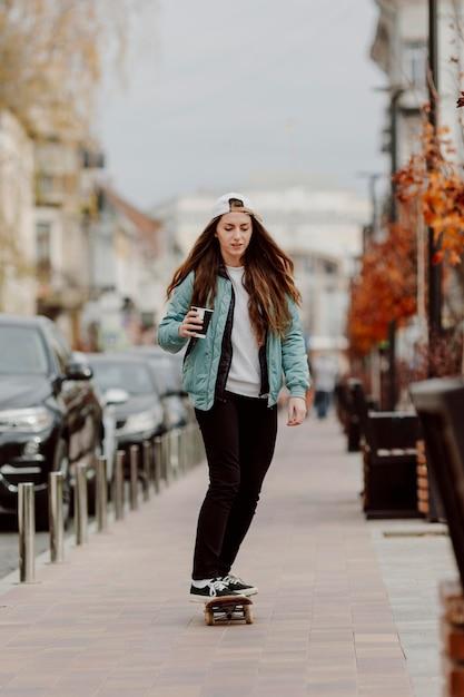 スケートに乗っている間コーヒーのカップを保持しているスケートボーダーの女の子 無料写真