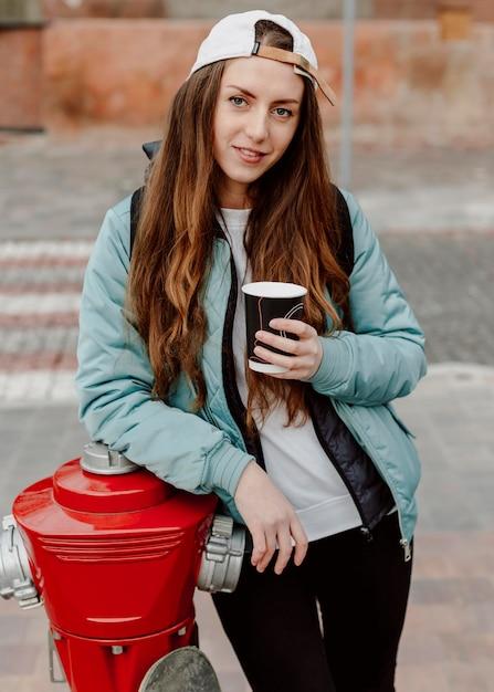 一杯のコーヒーを保持しているスケートボーダーの女の子 無料写真