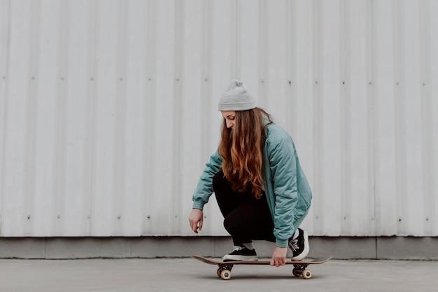 Ragazza di skateboarder in sella al suo skate in città Foto Gratuite