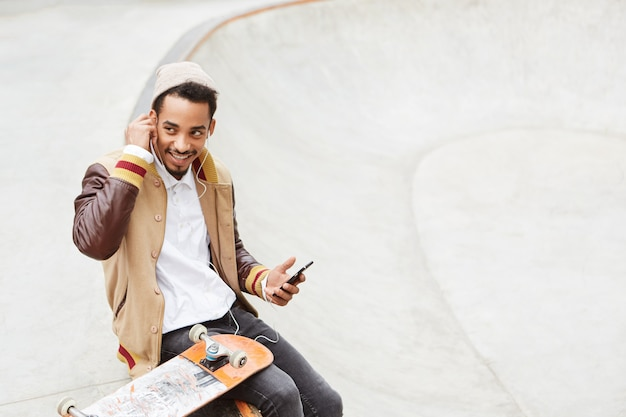 スケートボードのコンセプトです。スタイリッシュなのんきなティーンエイジャーはスケートボードをし、アクティブな一日の後に休憩します、 無料写真